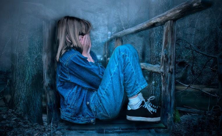 jeune fille recroquevillée dans un coin sombre